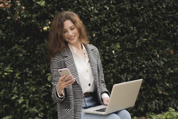 mujer sonriente usando telefono inteligente y