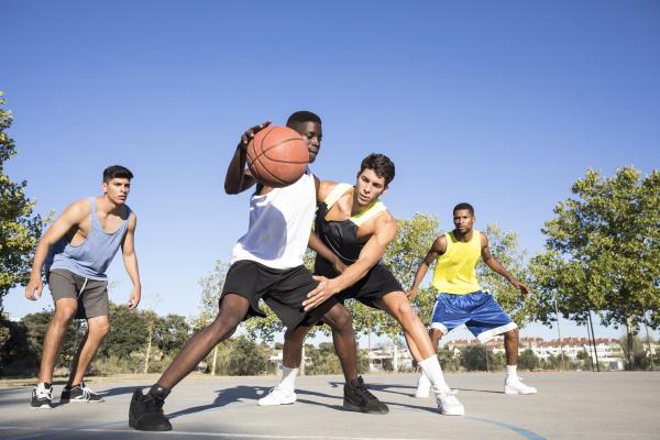 hombres jovenes jugando al baloncesto y