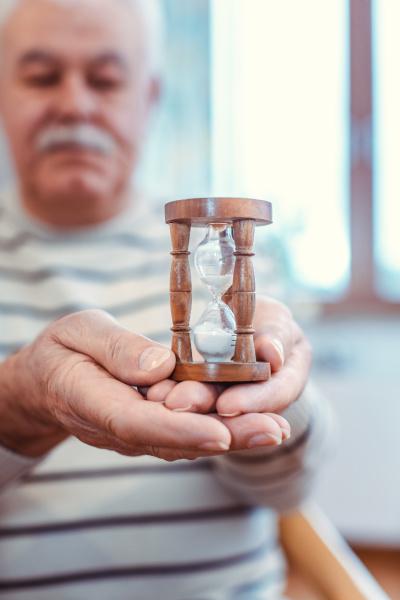 hombre mayor sosteniendo reloj de arena