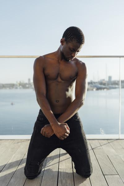 hombre negro arrodillado con las manos