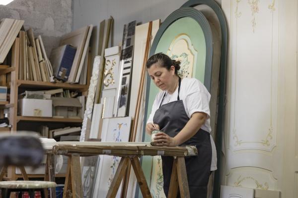 mujer madura pintando puerta mientras esta