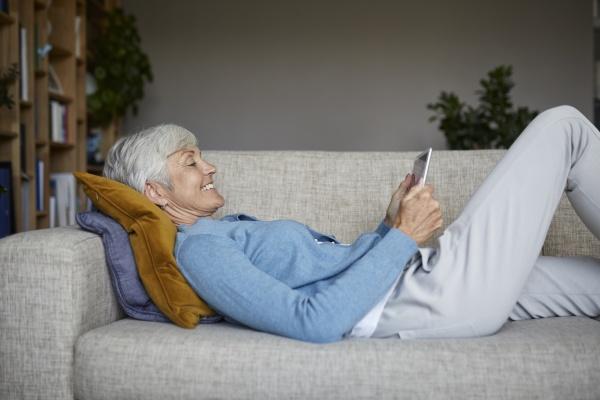 mujer sonriente usando una tableta digital