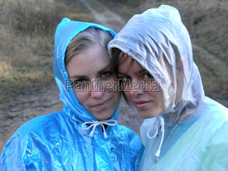 two girlfriends in raincoats