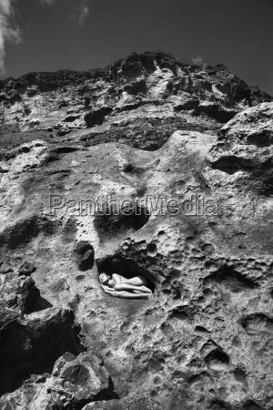 mujer desnuda sobre la roca