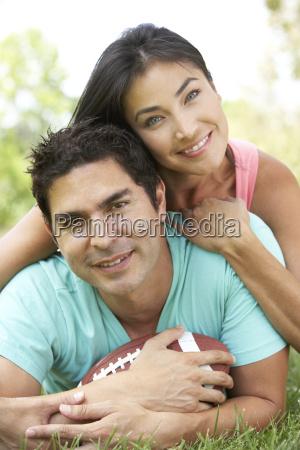 pareja en parque con futbol americano