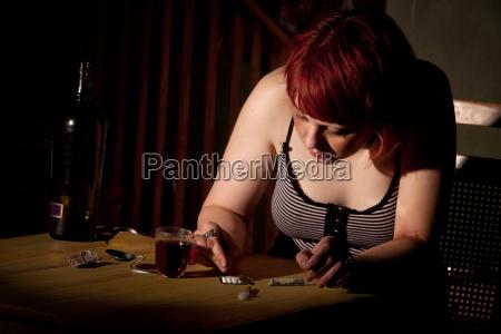 mujer joven cortando lineas de heroina