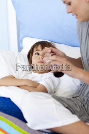 madre dando a su hijo acostado