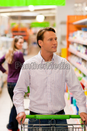 man and woman in supermarket