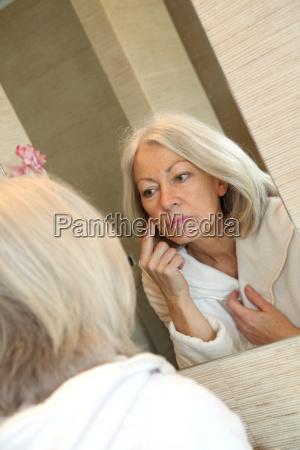 senior woman applying moisturizer on her