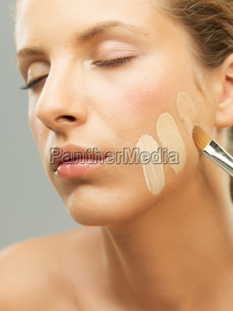 mujer tratando tonos de base en