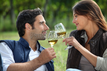 couple drinking wine in field