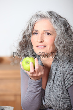 mujer madura hermosa comiendo manzana verde