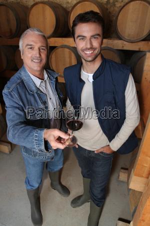 sonriendo viticultores en bodega