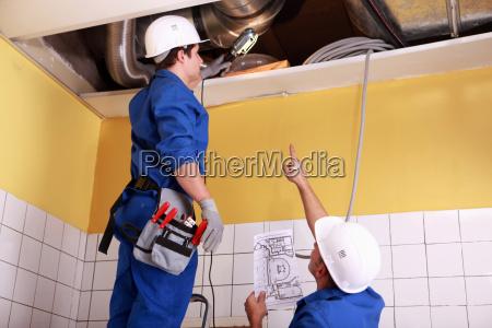 dos tecnicos revisando el aire acondicionado