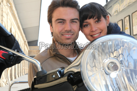 young couple smiling on a motorbike