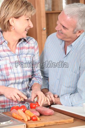 pareja madura preparando verduras