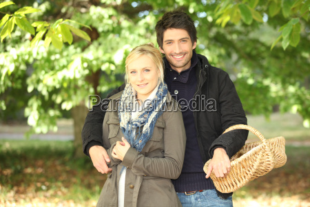 young couple behind trees in autumn