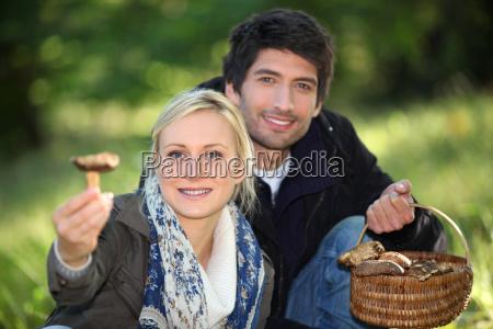 pareja recogiendo setas en un bosque