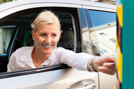 woman pushing parking ticket in parking