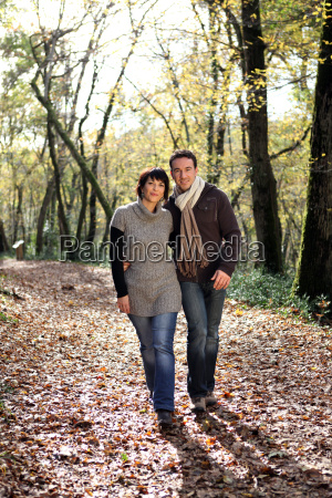 couple walking through park in autumn
