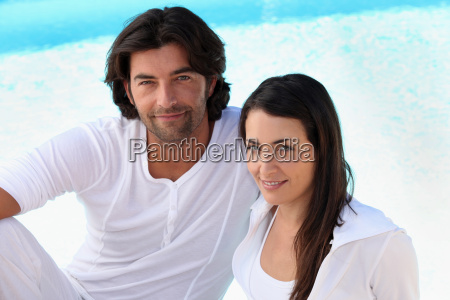 couple wearing white clothing sat by