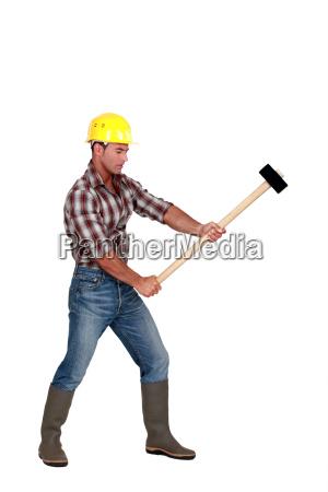 hombre usando martillo de trineo
