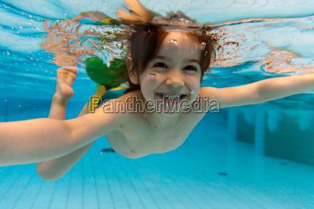 la chica sonrie nadando bajo el