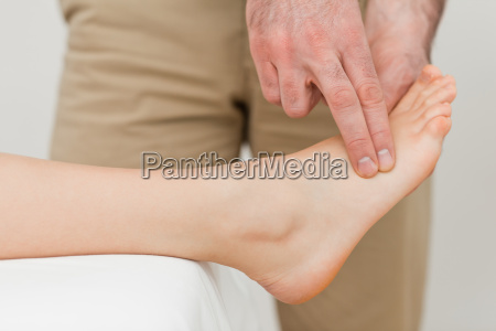 fingers of a physiotherapist pressing on