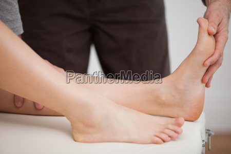 physiotherapist manipulating the foot of a