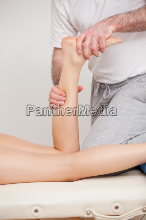 a doctor manipulating the ankle of
