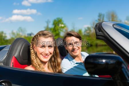 pareja joven con descapotable en verano