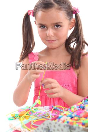 pequenya muchacha que hace el collar