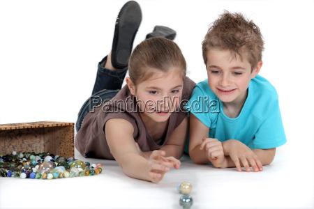 hermano y hermana jugando canicas juntos