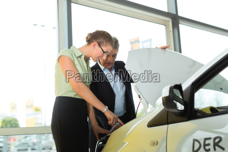 dealers and woman in dealership looking