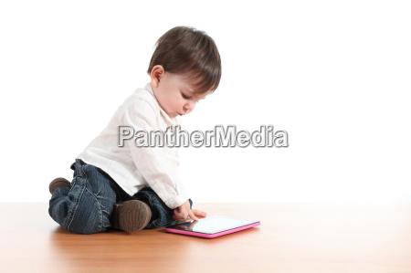 bebe jugando con una tableta digital