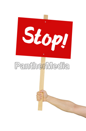 person holding sign reading stop