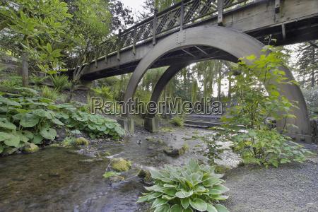 stream under the wooden bridge arches