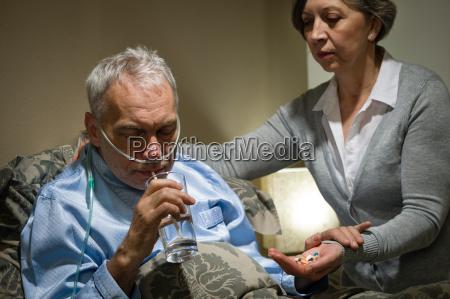 hombre mayor tomando medicamentos con agua