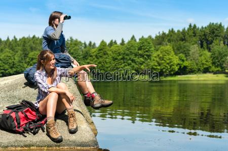 excursionistas adolescentes birdwatching en el lago