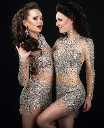 excitada pareja glamorosa en vestidos platino