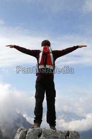 un escalador abre los brazos a