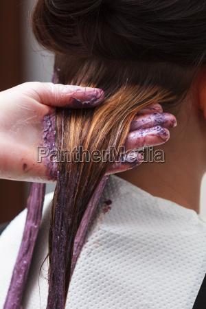 peluqueria aplicando color al cliente femenino