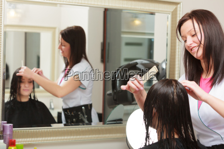 hairstylist combing hair woman client in