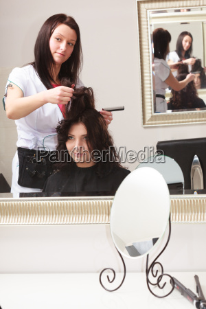 curly woman looking at a mirror