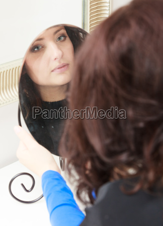 curly woman looking at mirror by