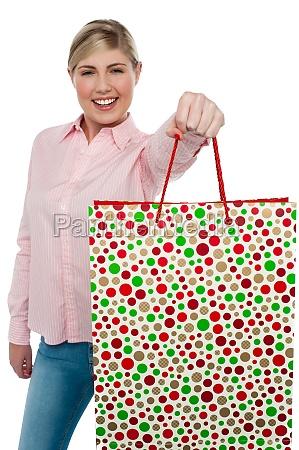 cheerful blonde girl holding shopping bag