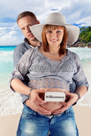 young pregnant couple on the beach