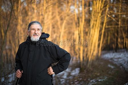 senior hombre marcha nordica disfrutando de