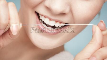 chica limpiando dientes con hilo dental