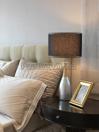 detail lamp and nightstand beside bed